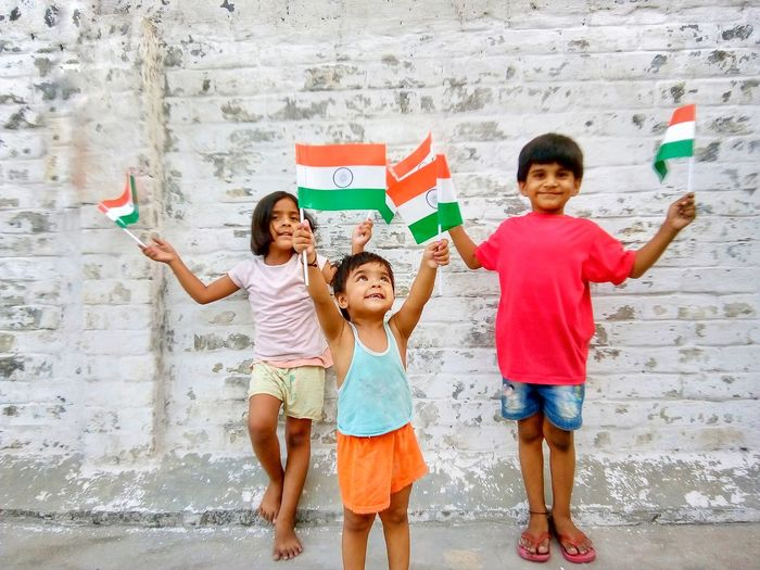 Happy friends holding small indian flags against wall