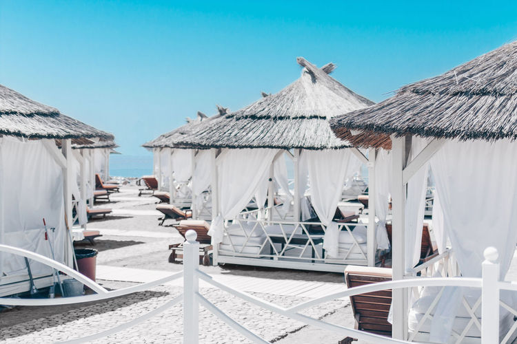 White gazebos with sofas on the beach for holidaymakers by the sea and ocean.