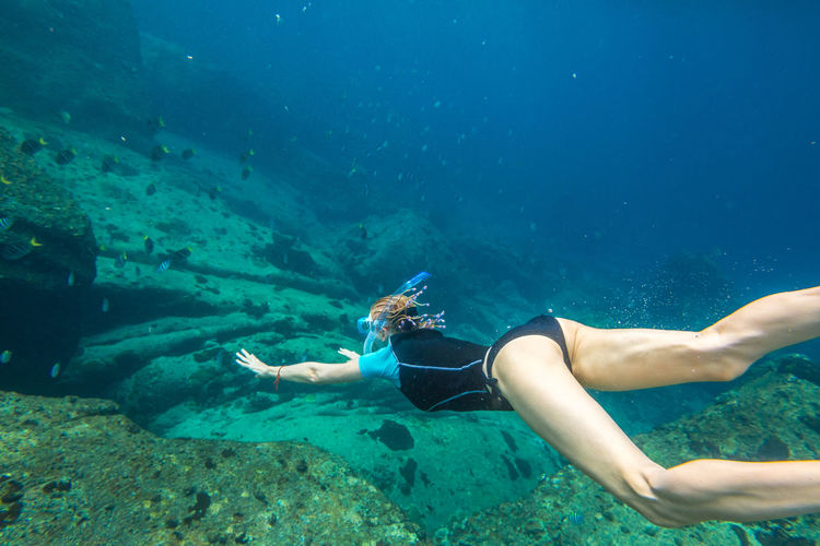 Woman snorkeling over coral reef undersea