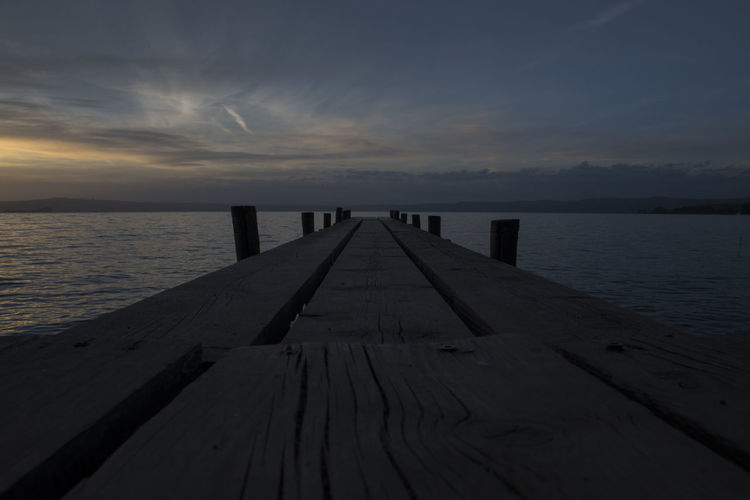 Wooden pier over sea against sky during sunset