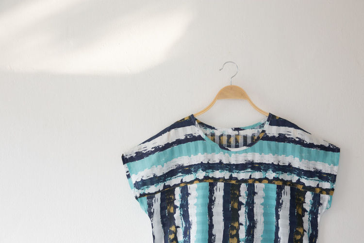 Close-Up Of Top Hanging In Coathanger On White Wall