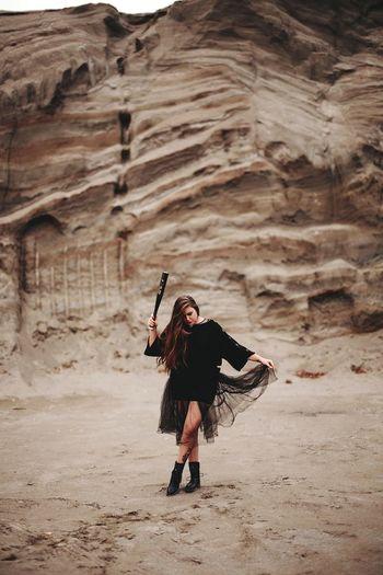 Full length of woman standing with baseball bat in desert against rock