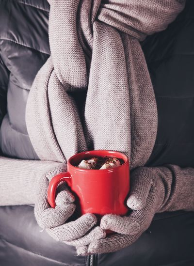 Close-Up Of Hand Holding Red Mug