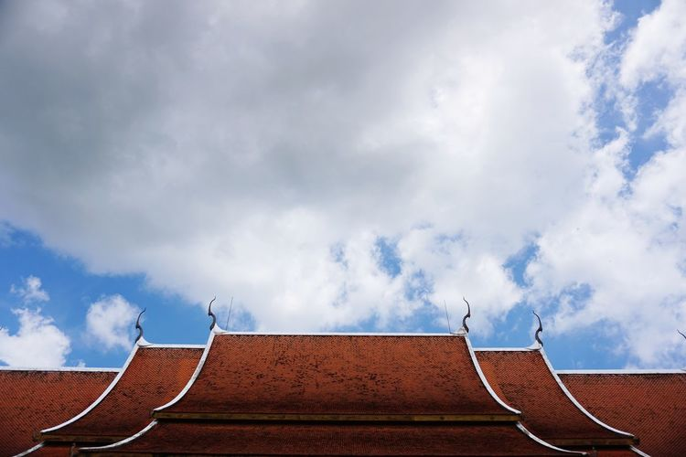 Low angle view of roof and building against cloudy sky