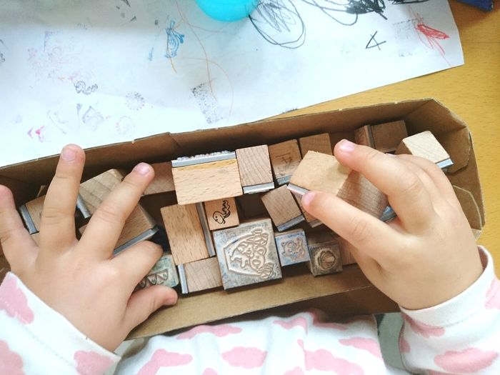 High angle view of baby hands holding wooden stamps in box on table