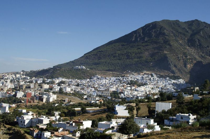 Aerial View Of Townscape By Mountains Against Blue Sky
