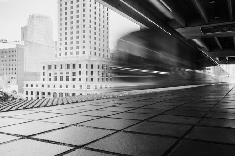 Blurred motion of train against buildings in city