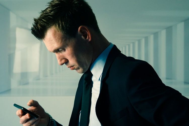 Businessman using smart phone in office building