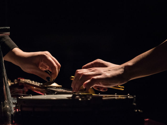 Cropped hands playing music against black background