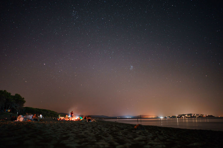 Bonfire Beach Beauty In Nature Fire Group Of People Illuminated Land Milky Way Nature Night Outdoors Real People Scenics - Nature Sky Space Star Star - Space Star Field Water HUAWEI Photo Award: After Dark