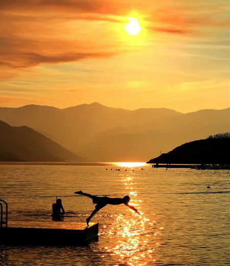 Golden sunset at Lake Chelan. Golden Golden Hour Sunset Silhouettes Sunset_collection Silhouette_collection Lifestyles Diving Diving Into Water Diving In  Swimming Swim Lake Lake Life Sun Silhouette Water Mountain Orange Color Sea Sunlight Outdoors Reflection Scenics Beauty In Nature Vacations Sky Sunset Tranquil Scene Idyllic Tranquility An Eye For Travel Summer Exploratorium The Traveler - 2018 EyeEm Awards Summer Sports