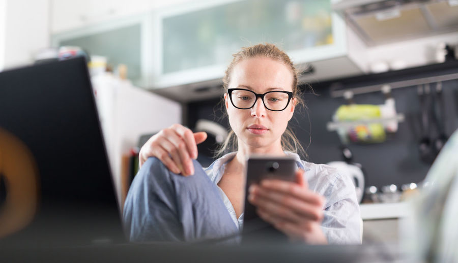 Business woman using smart phone while sitting at home