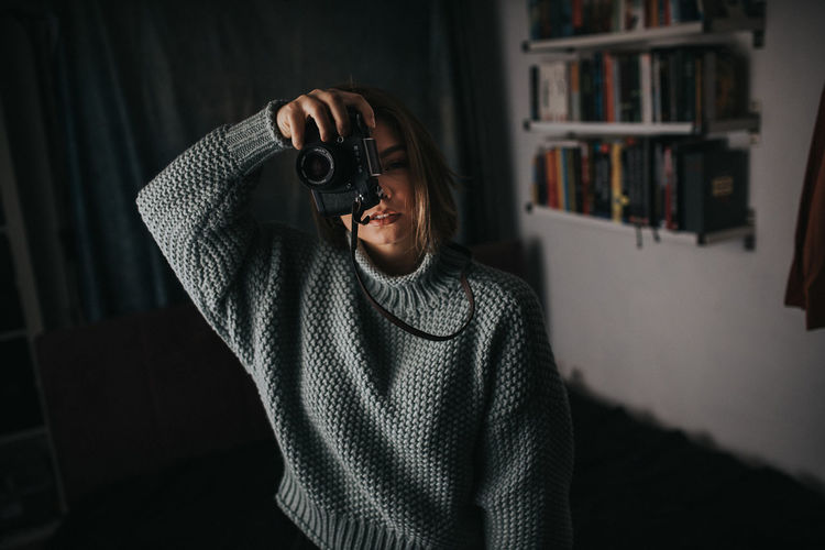 Full length portrait of man photographing at home