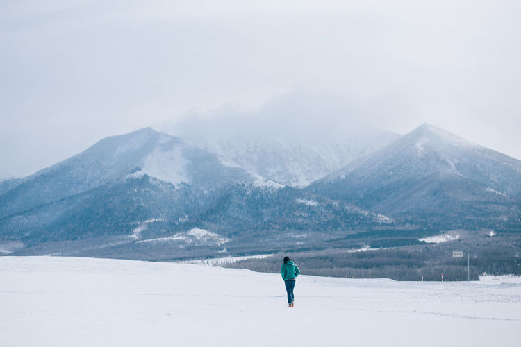 Rear view of woman walking on snowcapped mountain