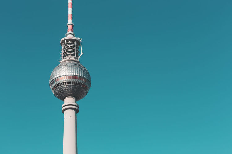 Low angle view of fernsehturm against clear turquoise sky