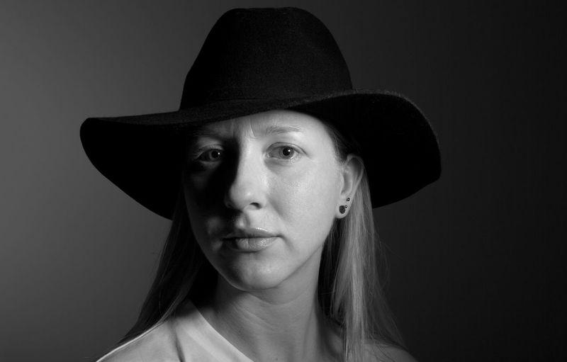 Portrait of woman wearing hat against black background