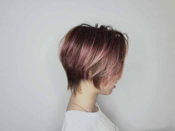 Side View Of Young Woman With Dyed Hair Against White Background