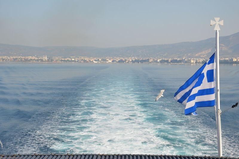Greek flag on boat in sea against sky