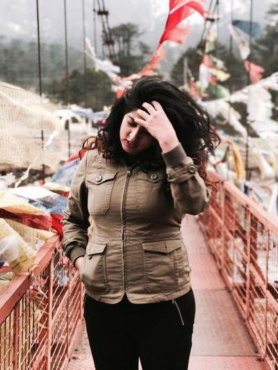 Young woman standing on footbridge on mountain