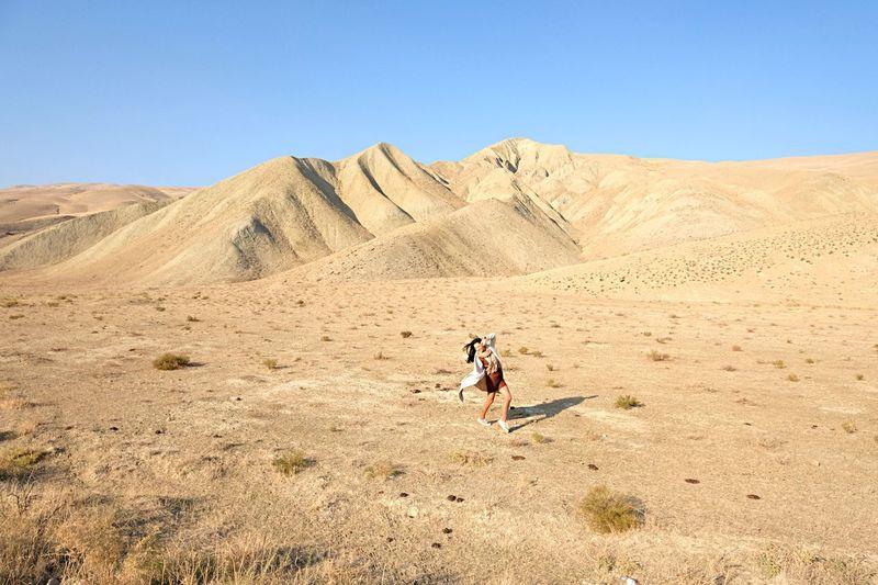 Full length of man on arid landscape against sky