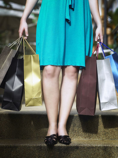 Low Section Of Woman Holding Shopping Bags While Standing On Steps