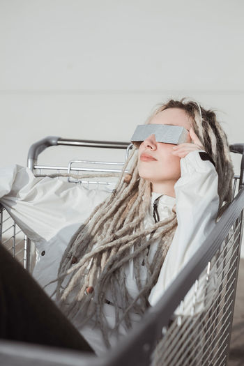 Fashionable young woman relaxing in shopping cart portrait One Person Indoors  Women Lifestyles Glasses Real People Adult Young Adult Young Women Females Portrait Looking Clothing Looking Away Blond Hair Holding Mid Adult Headshot Hairstyle Beautiful Woman