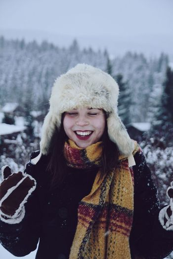 Cheerful young woman wearing warm clothing against trees during winter