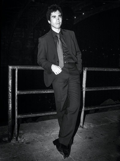 Young man looking away while standing against railing