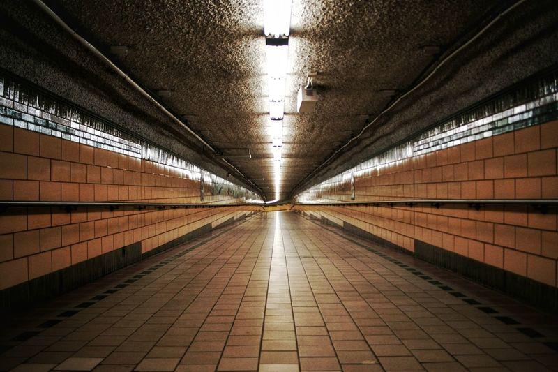 Interior of illuminated walkway at railroad station