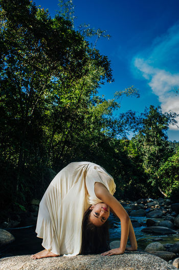 Side view of flexible woman bending over backwards on rock in forest