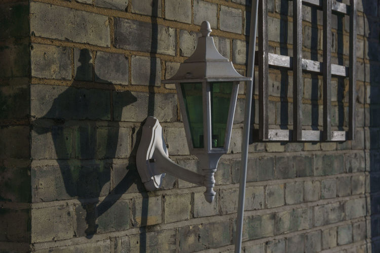 White applique lamp and shadow on the brick wall outside the building and empty flower hanger, shoot in golden hour Abandoned Applique Architecture Creative Light And Shadow Day Everything In Its Place Lamp Obsolete Old Outdoors Ruined Sconce Shadow Wall Wall - Building Feature Wall Lamp Sony A6000 Building Exterior EyeEm Masterclass Learn & Shoot: Simplicity Learn & Shoot: Composition Patterns & Textures Shadow-art Pastel Power Open Edit