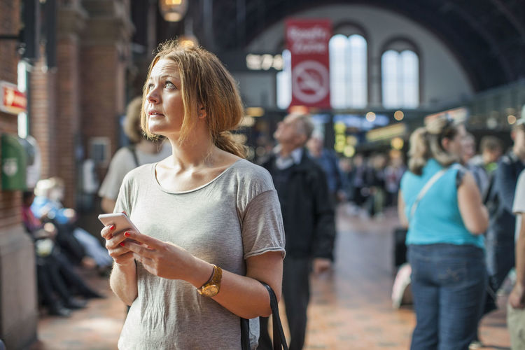 Woman standing on mobile phone in city
