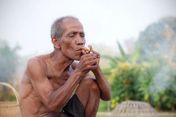 Shirtless senior man lighting bidi while sitting at farm