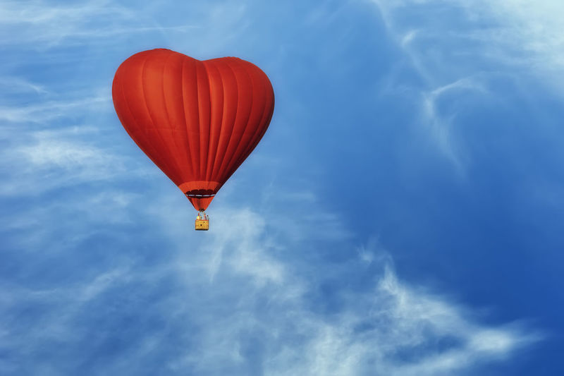 Red air balloon in the shape of heart against blue sky in a sunny bright day fly high above the tree