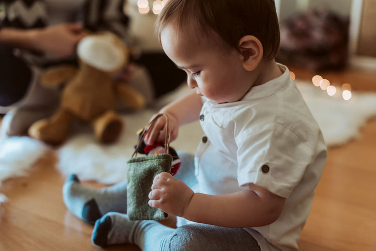 Cute boy playing with baby