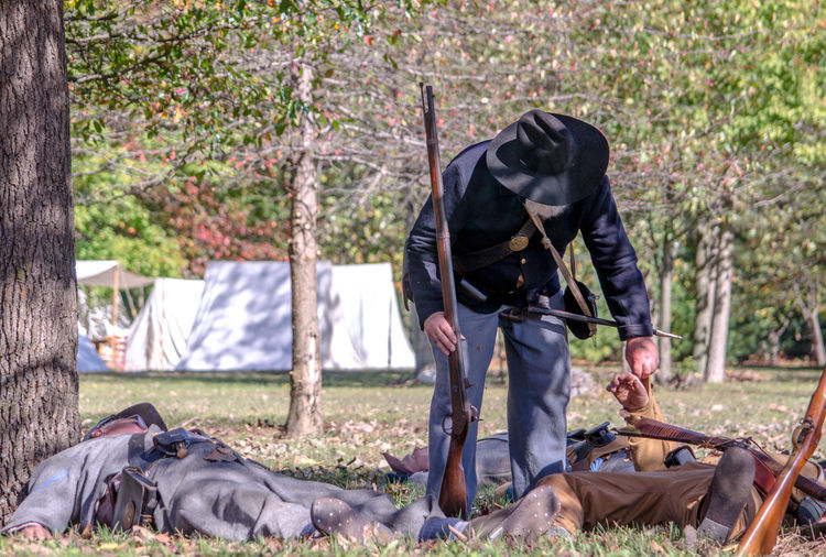 oct 8, 4th Annual Mooresville Civil War Days , South Haven, Michigan; a union soldier searches the dead and wounded during this civil war reenactment Acting Actors Camping Civil War Event Fight Michigan, USA Nature Soldiers USA Uniforms Union Bending Editorial  Guns History Lifestyles Men Military North Vs South Outdoors People Real People Reenactment Weopons
