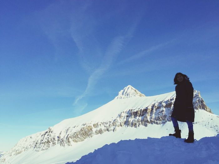 Rear view of person standing on snowcapped mountain against blue sky