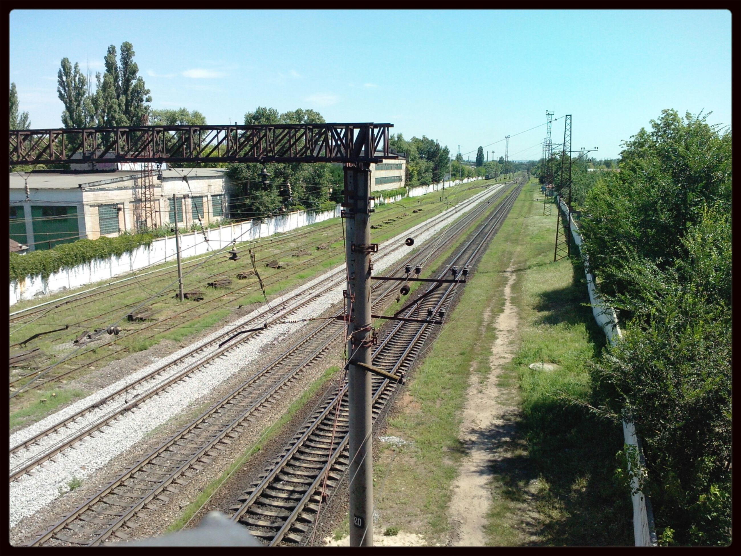railroad track, transfer print, rail transportation, transportation, tree, built structure, auto post production filter, architecture, the way forward, public transportation, clear sky, sky, diminishing perspective, building exterior, railway track, vanishing point, day, railroad station platform, high angle view, railroad station