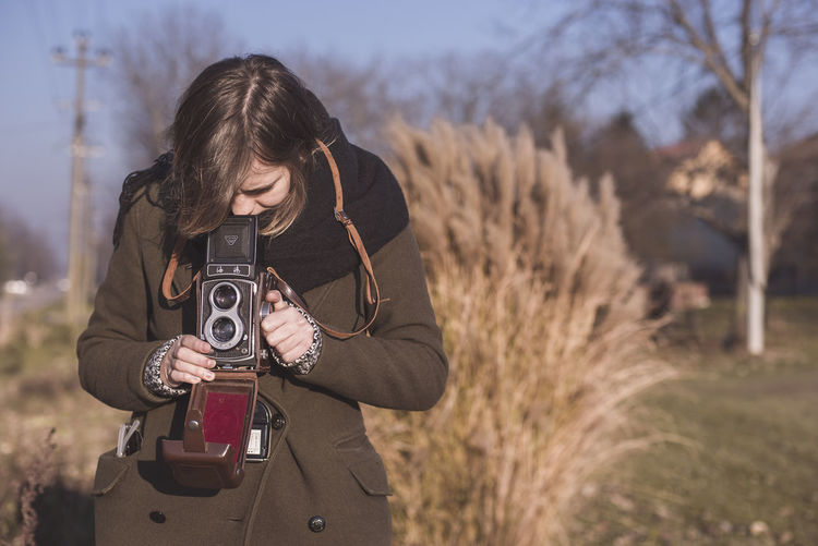Young woman photographing through camera on field