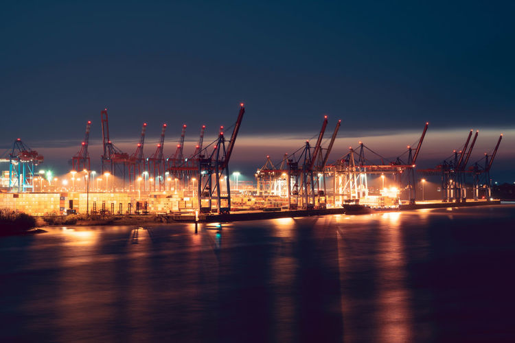 Illuminated pier at harbor against sky