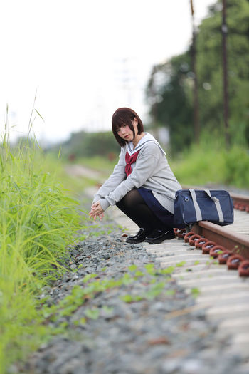 Portrait Of Young Woman In School Uniform Sitting On Railroad Track