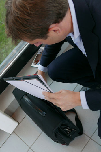 High Angle View Of Businessman Keeping Documents In Briefcase At Office Corridor