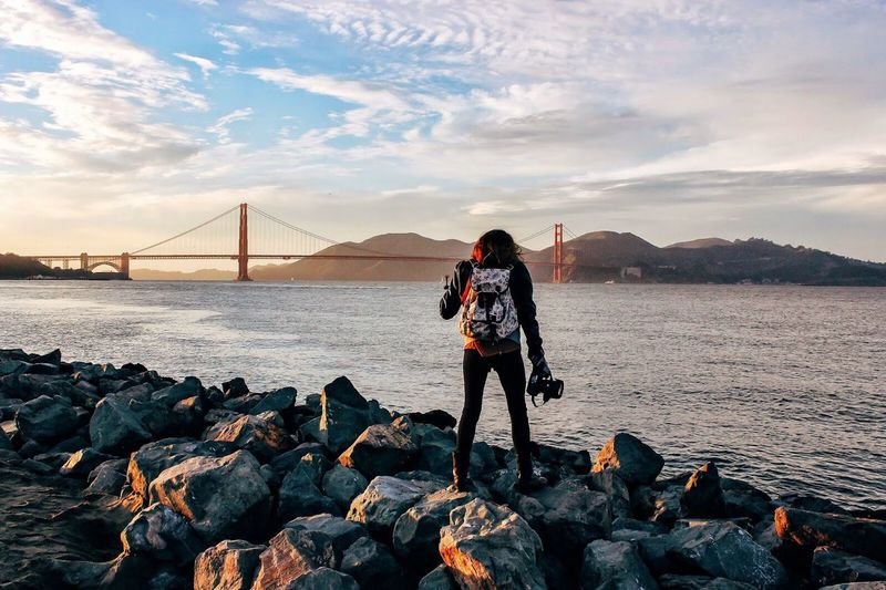 Rear view of woman standing on rocks by sea against golden gate bridge during sunset