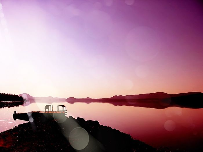 Scenic view of calm lake against clear purple sky
