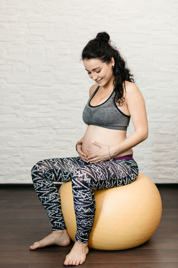 Happy pregnant woman sitting on a fitness ball and touching her belly. 20s Adult Copy Space Motherhood Relaxing Antenatal Caucasian Ethnicity Excersice Excersizing Fit Fitness Ball Health Healthy Mom To Be One Person Pregnancy Pregnant Prenatal Real People Relax Relaxation Smiling Touching Vertical Women Young Adult