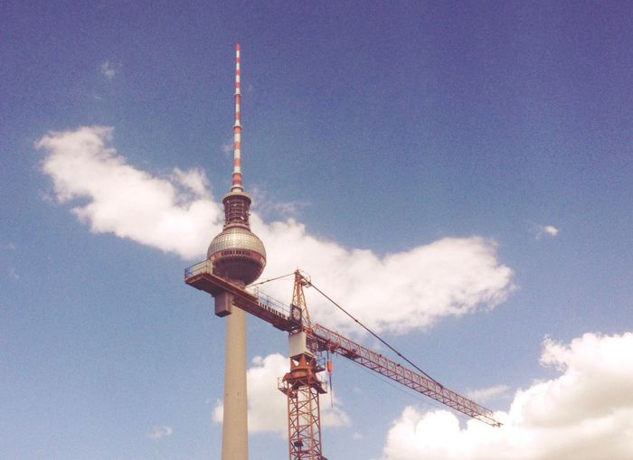 Low angle view of crane by fernsehturm against sky