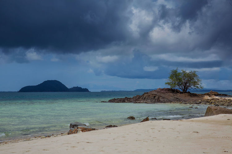 Beach Beauty In Nature Calm Cloud Cloud - Sky Cloudy Island Nature One Tree Outdoors Rock - Object Scenics Sea Shore Sky Strom Water