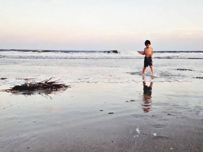 Boy standing on against sea at beach