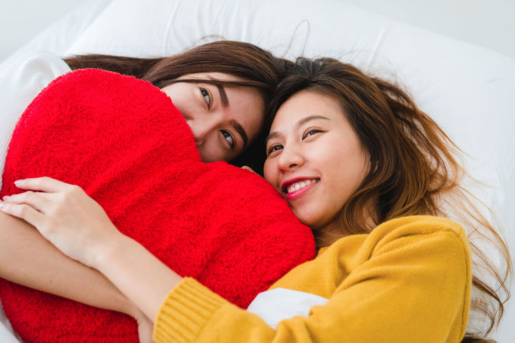 Women holding stuffed heart shape while lying on bed at home