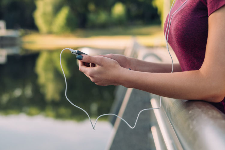 Cropped shot of woman using mobile phone and listening music, outdoor Copy Space Summertime Communication Connection Day Focus On Foreground Healthy Lifestyle Holding Human Body Part Human Hand Leisure Activity Lifestyles Midsection Mobile Phone Music One Person Outdoors Portable Information Device Real People Sexygirl Smart Phone Technology Using Mobile Wireless Technology